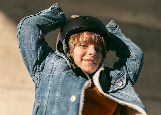 그의 자전거를 타기위한 안전 헬멧을 가진 웃는 소년
