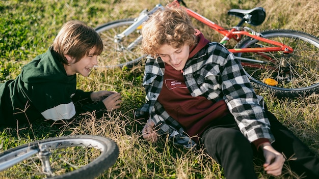 Smiley boys relaxing on grass while riding their bikes