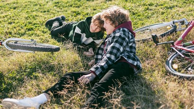 自転車に乗っている間草の上で休んでいるスマイリーの男の子