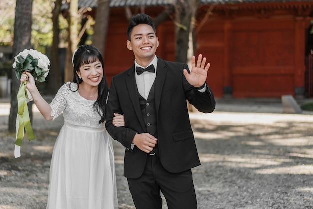 결혼 후 손을 흔드는 웃는 신부와 신랑