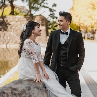 Smiley bride and groom outdoors together