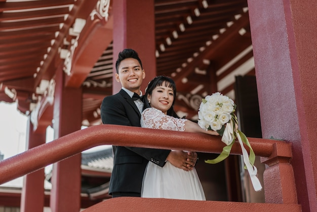 Smiley bride and groom posing together outdoors