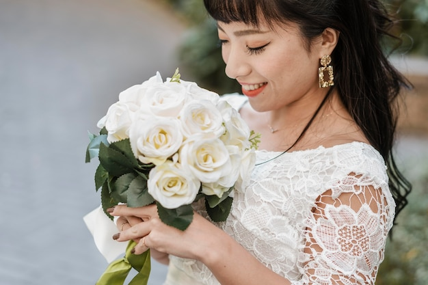Smiley bride holding bouquet of flowers outdoors
