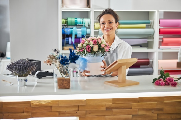 Smiley brunette florist posing with a flower-pot of roses