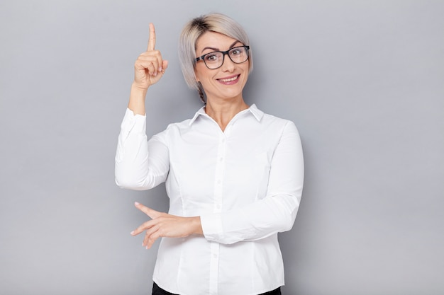 Smiley business woman pointing above