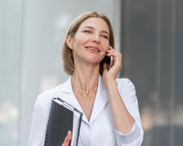 Donna di affari di smiley che parla sul telefono