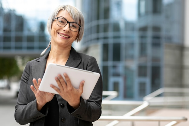 Smiley business woman using tablet