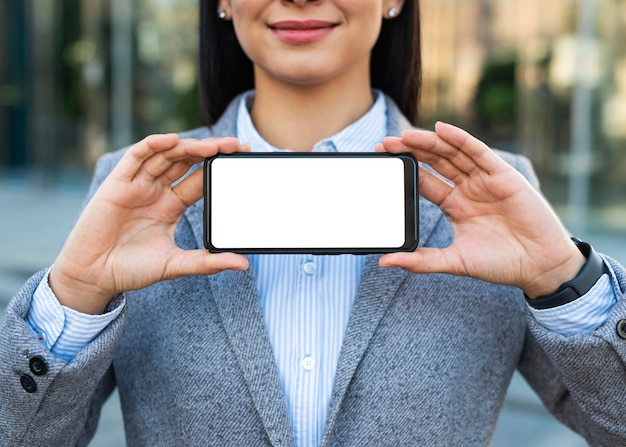 Smiley businesswoman holding smartphone