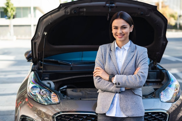 Smiley businesswoman posing next to car with open hood