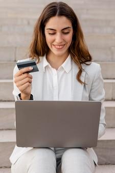 Смайлик бизнесвумен, делая покупки в интернете с ноутбуком и кредитной картой