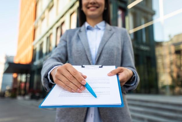 Donna di affari di smiley che ti mostra dove firmare negli appunti