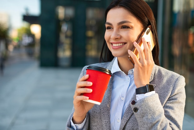 Smiley businesswoman talking on the phone while having coffee in the city