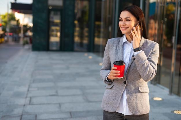 Donna di affari di smiley che parla sul telefono mentre beve caffè con lo spazio della copia