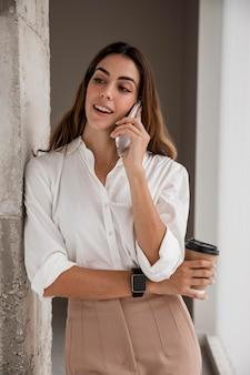 Donna di affari di smiley parlando al telefono mentre beve il caffè