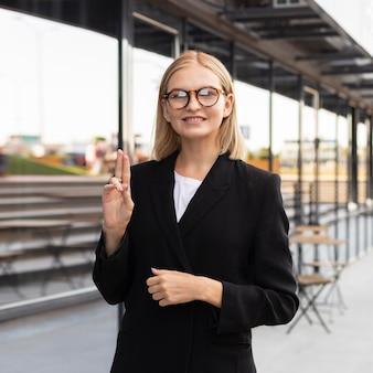 Imprenditrice di smiley utilizzando il linguaggio dei segni all'aperto al lavoro