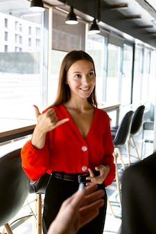 Smiley businesswoman using sign language at work