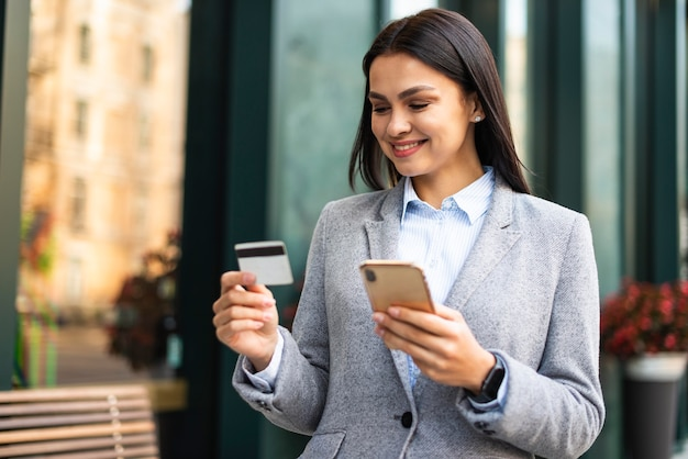 Smiley businesswoman using smartphone and credit card outdoors