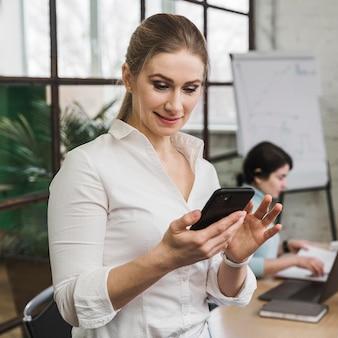Смайлик бизнесвумен с помощью смартфона во время встречи