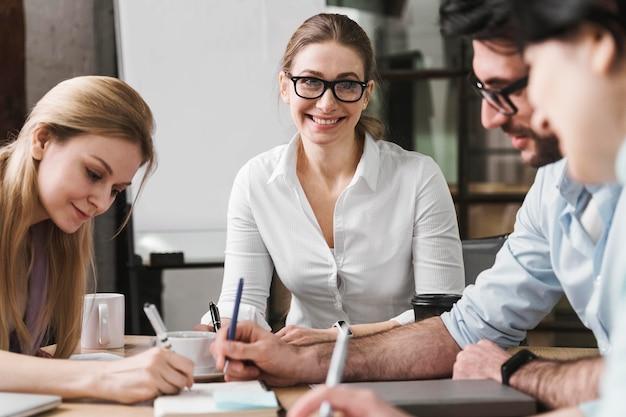 Smiley imprenditrice con gli occhiali durante una riunione