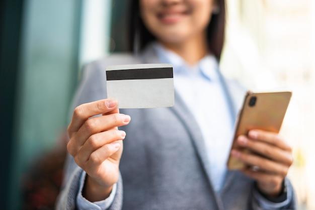 Смайлик бизнесвумен со смартфоном и кредитной картой на открытом воздухе