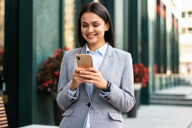Smiley businesswoman with smartphone outdoors