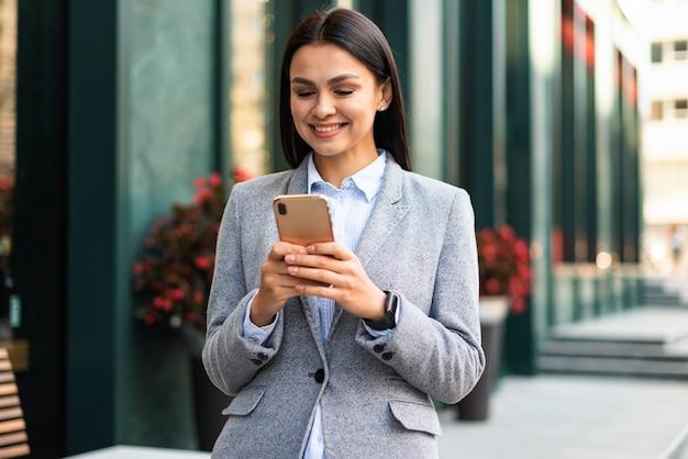 屋外でスマートフォンを持つスマイリー実業家
