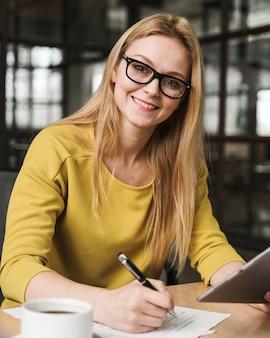 Donna di affari di smiley che lavora allo scrittorio