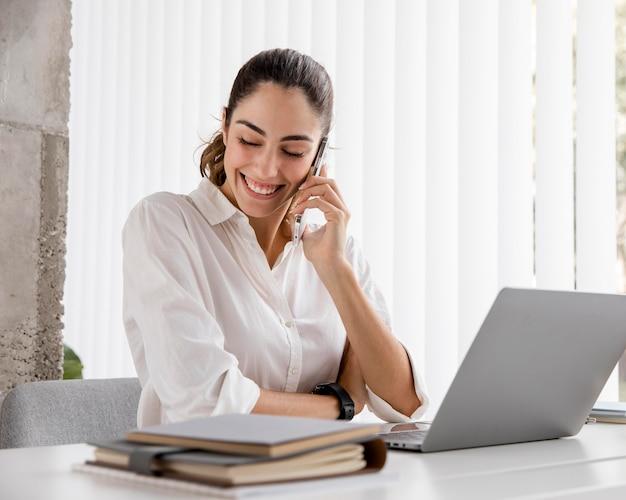 Donna di affari di smiley che lavora con smartphone e laptop