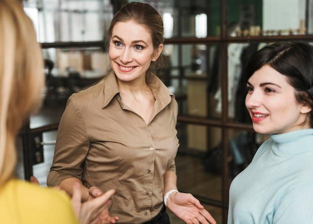 Смайлик деловых женщин обсуждают в помещении
