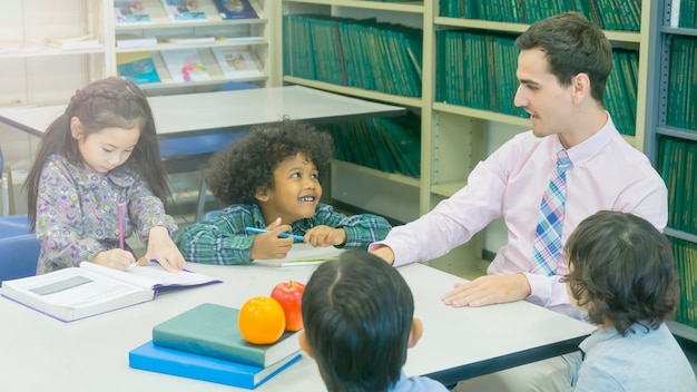 Smiley caucasian teacher and grouping of asian kids student learning
