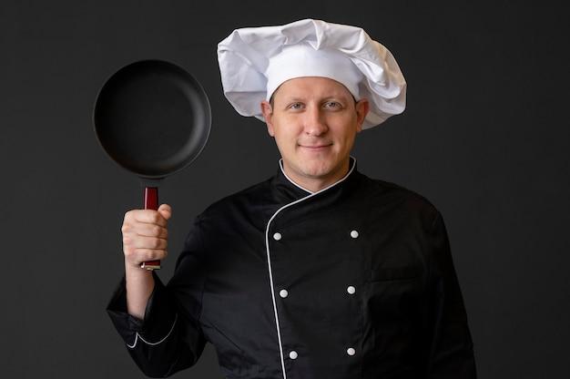 鍋を持っているスマイリーシェフ
