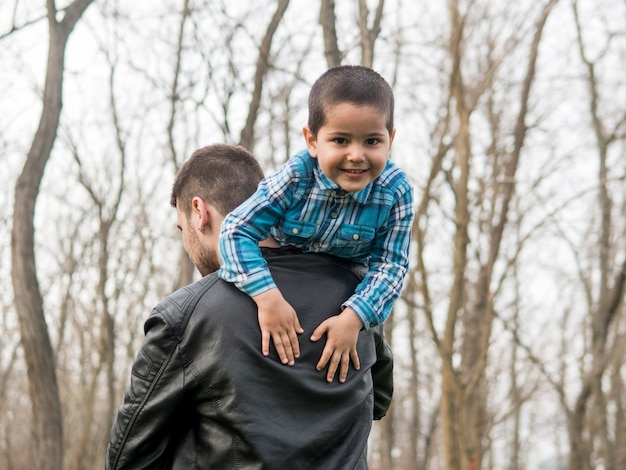 Smiley child being held by his father outdoors