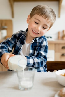 Smiley child pouring milk in glass