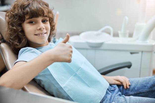 치과 의사 약속을 기다리는 치과 의자에 앉아있는 동안 엄지 손가락을 들고 밤나무 곱슬 머리를 가진 웃는 아이
