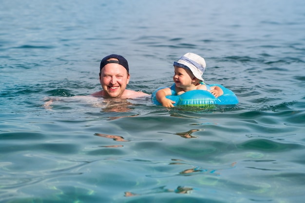 A smiley child with his dad swims in a swimming ring in the blue sea