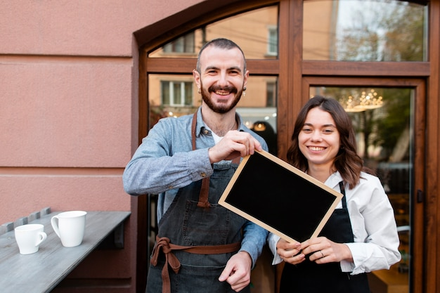 Smiley coffee shop owners holding frame