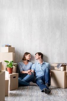 Улыбающаяся пара дома, собирая вещи, чтобы выехать