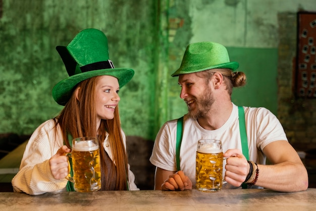 Smiley couple celebrating st. patrick's day at the bar