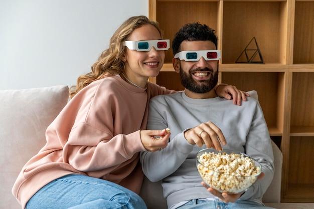 팝콘을 먹고 3 차원 안경으로 집에서 영화를 보는 웃는 커플