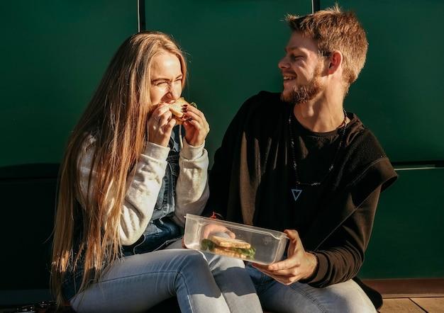 Смайлик пара вместе едят на открытом воздухе