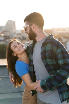 Smiley couple embrace outdoors in the city