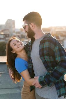 スマイリーカップルが街の屋外で抱擁