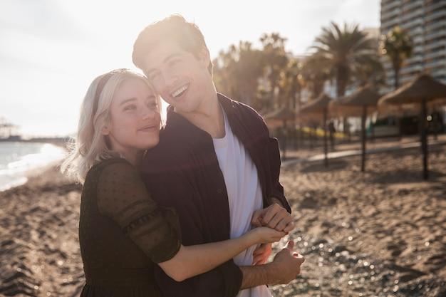 Улыбающаяся пара обнимается на пляже