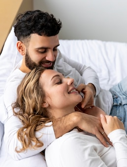 Smiley couple embraced in bed at home