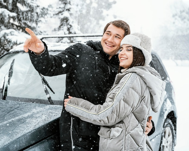 Smiley couple embracing in the snow while on a road trip