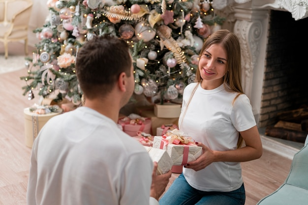 Smiley couple exchanging presents in front of christmas tree