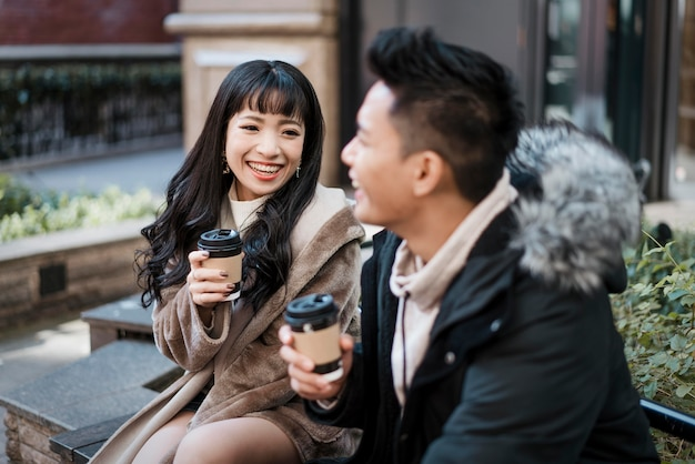 Smiley couple having coffee and talking outdoors