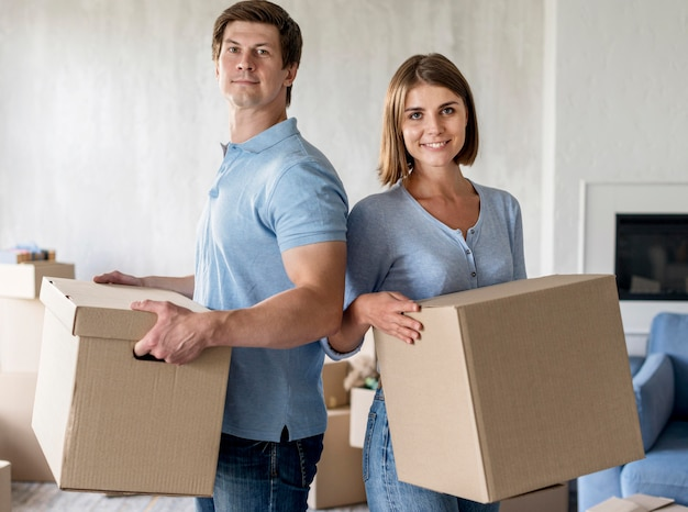 Smiley couple holding boxes in moving out day