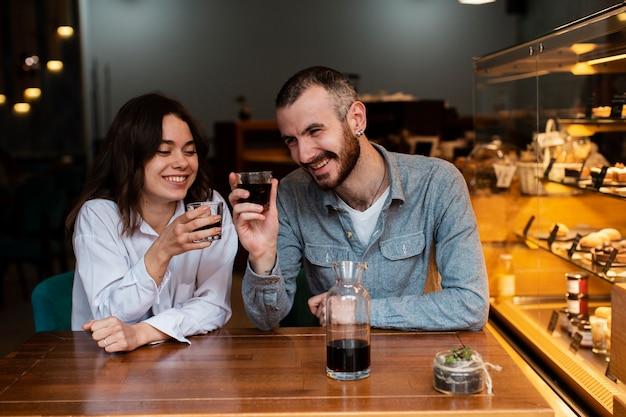 Smiley couple holding glasses of coffee
