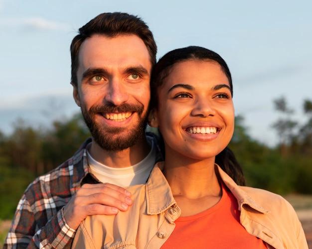 美しい夕日を見ているスマイリーカップル